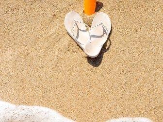 Flip Flops und Sonnencreme werden von einer Welle gewaschen