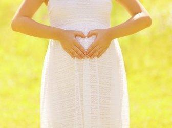 Sunny Konzept schwangeren Frau, die Hände in Form von Herzen