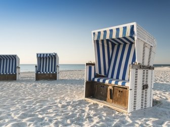 Strand-Stühlen auf der Insel Sylt auf den Sonnenuntergang. Deutschland.