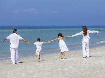 Mutter, Vater und Kinder laufen am Strand