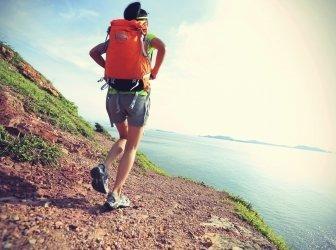 Weibliche Wanderin klettert auf Bergwanderweg am Meer