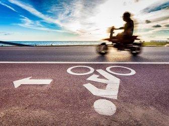 Fahrradstraßenschild mit Mottorrad bei Sonnenuntergang