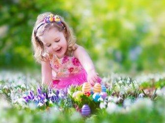 Glückliches kleines Mädchen bei der Eiersuche