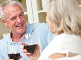 Happy Senior Mann & Frau paar trinken Wein zu Hause fühlen