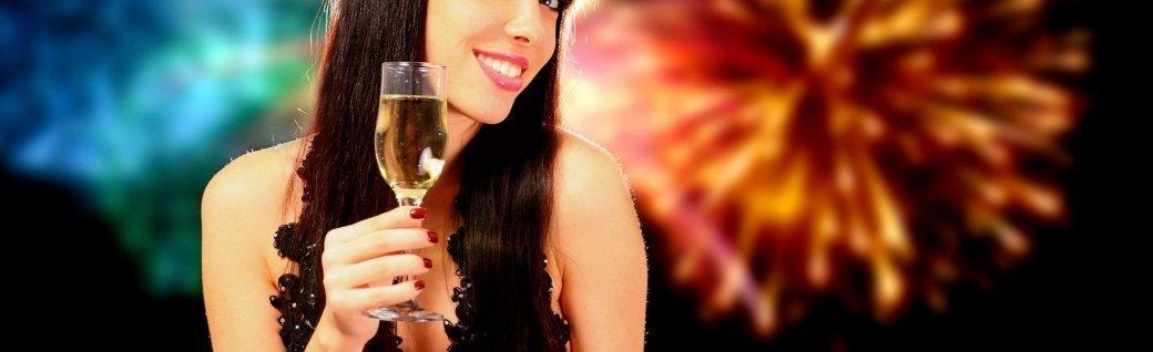 Sexy Frau mit Champagner, Feuerwerk im Hintergrund, Quelle: EmiliaU/istockphoto
