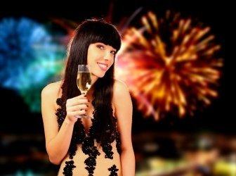 Sexy Frau mit Champagner, Feuerwerk im Hintergrund