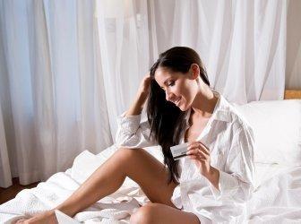Hispanic Frau sitzend im Bett shopping auf internet