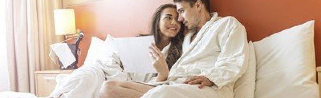 Junges Paar liegt im Bett in einem Hotelzimmer, Quelle: ©Geribody/istockphoto