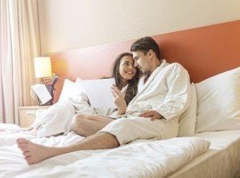Junges Paar liegt im Bett in einem Hotelzimmer