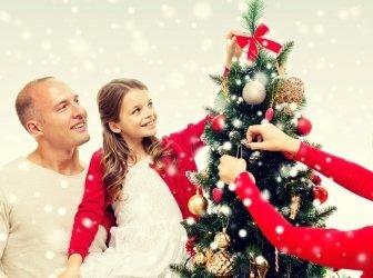 Lachende Familie schmückt den Weihnachtsbaum zu Hause