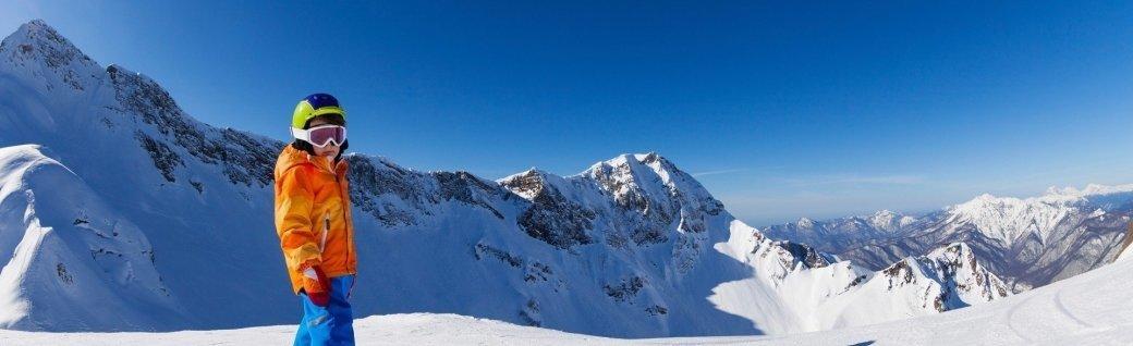 Junge Skifahren bei Sonnenschein mit Blick auf die Berge, Quelle: SerrNovik/istockphoto