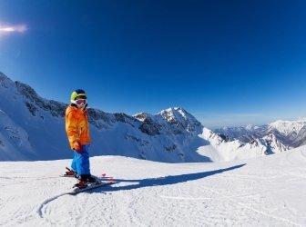 Junge Skifahren bei Sonnenschein mit Blick auf die Berge