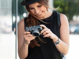 Der lachende Student fotografiert mit digitaler Spiegelreflexkamera