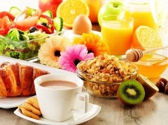 Frühstück mit Kaffee, Orangensaft, Croissants, Salat, Müsli