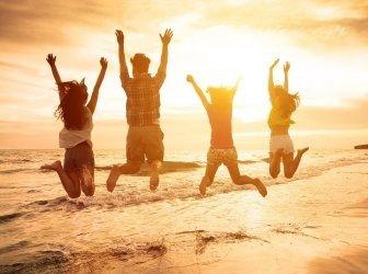Gruppe von jungen Leuten springt am Strand
