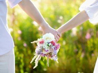 Junges Paar hält Wildblumenstrauß