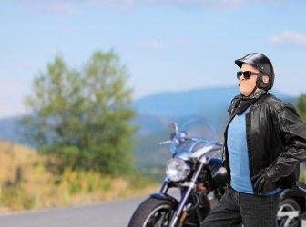älterer Biker läuft vor seinem Motorrad