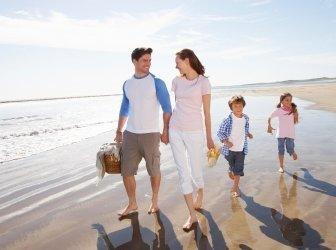 Familie gehen am Strand mit Picknick-Korb