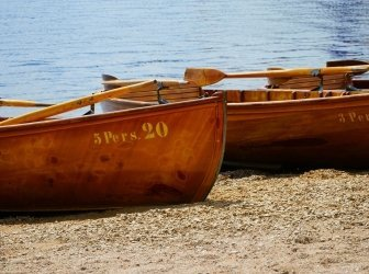Holzruderboote am Ufer des Sees